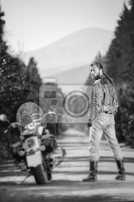 Motociclista con el pelo largo de pie cerca de su motocicleta de crucero por encargo en el camino abierto. Mirando a la cámara. Vista desde la parte posterior. Efecto suave de cambio de inclinación. E