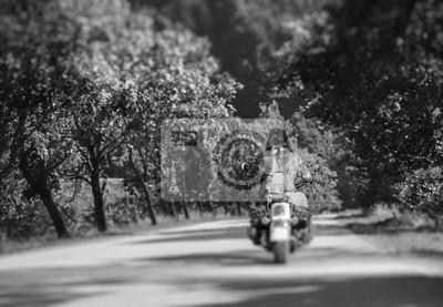 Motociclista con pelo largo caballo moto en carretera en el bosque. Vista desde la parte posterior. Efecto de desenfoque de la lente de cambio de inclinación. En blanco y negro