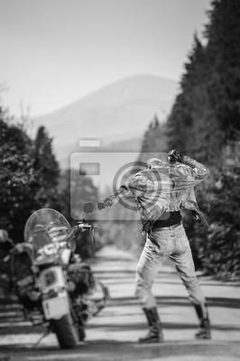 Motociclista con pelo largo llevaba chaqueta de cuero, botas y guantes de pie cerca de su motocicleta crucero por encargo en el camino abierto y el baile. Vista desde la parte posterior. Incline el ef