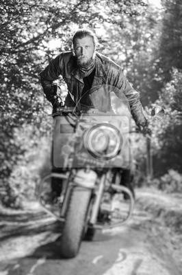 Motociclista concentrado con barba conduciendo su moto crucero en el bosque. El hombre lleva chaqueta de cuero y vaqueros. Efecto de desenfoque de la lente de cambio de inclinación. En blanco y negro