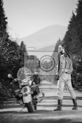 Motociclista hermoso con el pelo largo que desgasta la chaqueta de cuero, los pantalones vaqueros, las botas y los guantes que se colocan cerca de su motocicleta de crucero por encargo en la carretera
