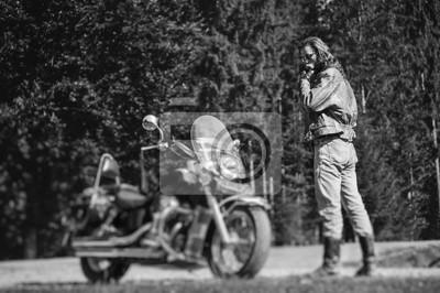 Motociclista hermoso con el pelo largo y la barba de pie cerca de su motocicleta de crucero por encargo mirando hacia abajo. Biker está usando chaqueta y gafas de sol en día soleado. Efecto suave de c