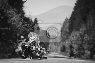Motociclista hermoso con la barba y el pelo largo que se sientan al lado de su motocicleta de crucero por encargo en un camino abierto. Guy está mirando a distancia. Efecto suave de cambio de inclinac
