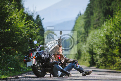 Motociclista hermoso con la barba y el pelo largo que se sientan al lado de una motocicleta del viajero en un camino abierto. El individuo está llevando la chaqueta de cuero y los tejanos. Día soleado