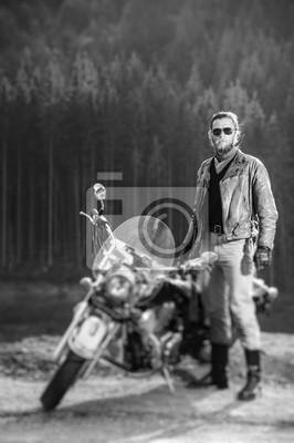 Motociclista hermoso de pie por su motocicleta de crucero en un día soleado con bosque en el fondo. El hombre lleva chaqueta de cuero y gafas de sol. Foto vertical. Efecto de desenfoque de la lente de