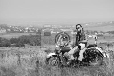 Motorista brutal con la barba que desgasta la chaqueta de cuero y las gafas de sol que se sientan en su motocicleta en un día asoleado, sosteniendo el casco. Imagen horizontal. Efecto de desenfoque de