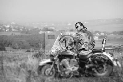 Motorista brutal con la barba que desgasta la chaqueta de cuero y las gafas de sol que se sientan en su motocicleta en un día asoleado, sosteniendo el casco. Imagen horizontal. Vista trasera. Efecto d