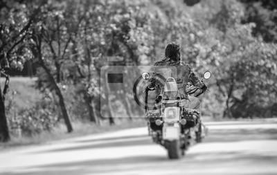 Motorista fresco con motocicleta de montar a caballo largo en el camino. Vista desde la parte posterior. Efecto de desenfoque de la lente de cambio de inclinación. En blanco y negro