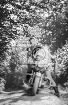 Motorista serio con la barba que conduce su motocicleta del crucero en el bosque. El hombre lleva chaqueta de cuero y vaqueros. Efecto de desenfoque de la lente de cambio de inclinación. En blanco y n