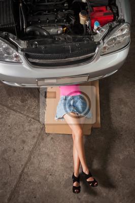 Muchacha atractiva con las piernas largas que mienten bajo el coche que controla el motor en