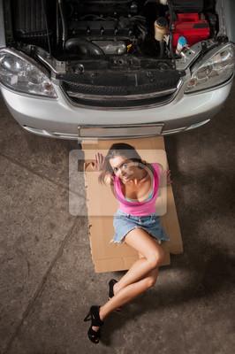 Muchacha atractiva con las piernas largas que se sientan cerca del coche en el taller de reparación del coche
