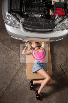 Muchacha atractiva que miente bajo el coche que controla el motor con el ligh constante