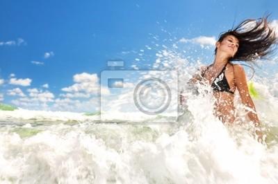 Muchacha hermosa que salpica en el océano