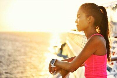 Póster Mujer activa relajante después de ejecutar en cruceros mirando el mar durante las vacaciones de verano. Corredor asiático niña vistiendo smartwatch monitor de actividad de ritmo cardíaco que viven un