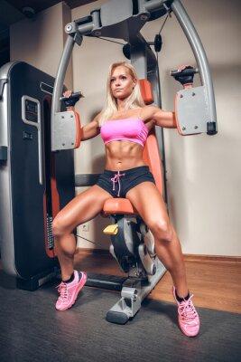 Póster mujer atractiva en gimnasia en la máquina del entrenamiento
