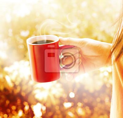 Mujer con la taza de café roja vibrante fondo marrón