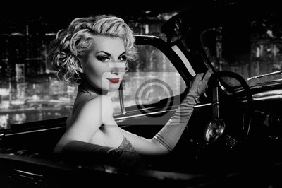 Mujer con los labios rojos en coche retro contra la ciudad de noche