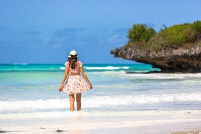 Mujer de cabello negro con un sombrero en una increíble playa de agua azul en Zanzíbar en Tanzania