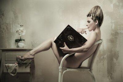 Póster Mujer desnuda sentada en una silla leyendo un libro en el interior