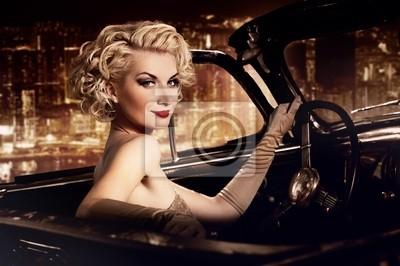 Mujer en el coche retro contra la ciudad de noche.