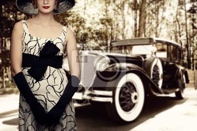Mujer en el sombrero contra el coche retro.