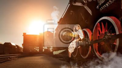 Mujer en el vestido de la vendimia está sentado en la rueda de la locomotora