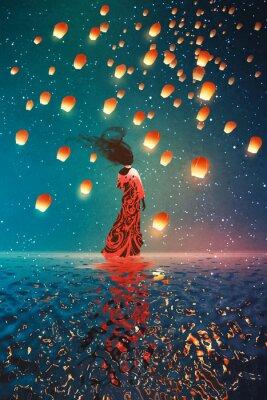 Póster Mujer en vestido de pie sobre el agua contra las linternas flotando en un cielo nocturno, pintura de ilustración