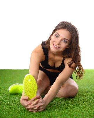 Póster Mujer haciendo ejercicios de estiramiento en la hierba verde