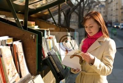 Mujer hermosa en París la selección de un libro en un booksel aire libre