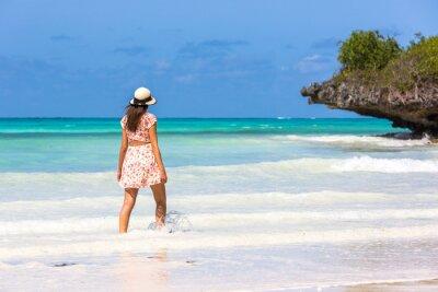Mujer joven con un sombrero en una increíble playa de agua azul en Zanzíbar en Tanzania