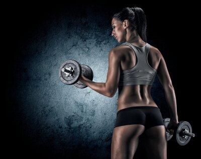 Póster Mujer muscular en el estudio sobre fondo oscuro