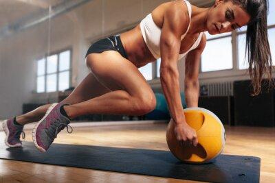 Póster Mujer muscular que hace intenso entrenamiento de la base en el gimnasio