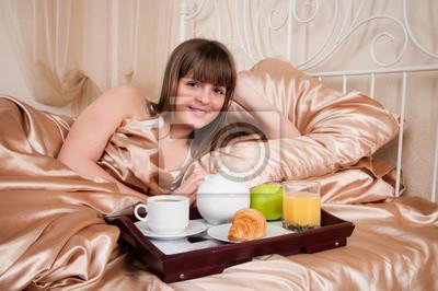 Mujer que come el desayuno y beber café en la cama. Mujer joven s