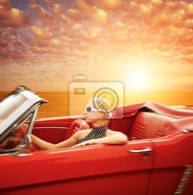 Mujer que conduce el coche retro contra el cielo hermoso.