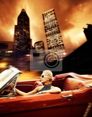 Mujer que conduce el coche retro en la ciudad moderna.