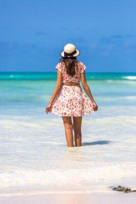 Mujer que llevaba un sombrero en una increíble playa de agua verde en Zanzíbar en Tanzania