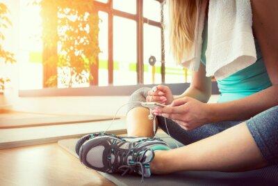Póster Mujer rubia atractiva con el teléfono inteligente, descansando después del entrenamiento de la gimnasia