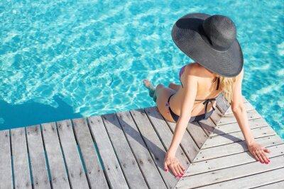 Póster Mujer sentada en la terraza junto a la piscina