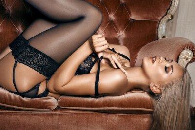 Póster mujer sexy en ropa interior negro seductora acostado en un sofá en medias