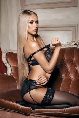 Póster mujer sexy en ropa interior negro seductora sentada en un sofá en medias
