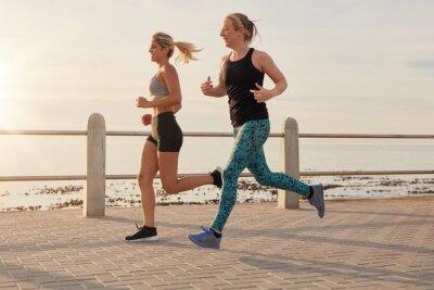 Póster Mujeres jóvenes corriendo por un paseo marítimo