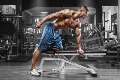 Póster Muscular hombre que trabaja en el gimnasio haciendo ejercicios con pesas en el tríceps, torso desnudo masculino fuerte abs