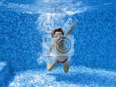 Niño bajo el agua después de saltar a la piscina