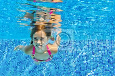 Niño feliz nada bajo el agua en la piscina, diversión en familia de vacaciones