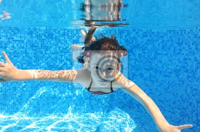 Niño feliz nada bajo el agua en la piscina, muchacha que se divierte
