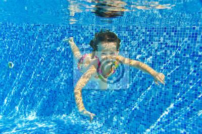 Niño sonriente feliz bajo el agua en la piscina, vacaciones de verano