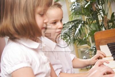 Niños que juegan el piano