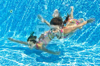 Niños sonriendo feliz subacuática en piscina en vacaciones