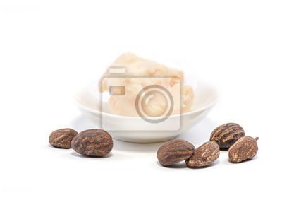Nueces de mantequilla de shea y una taza de manteca de karité en blanco