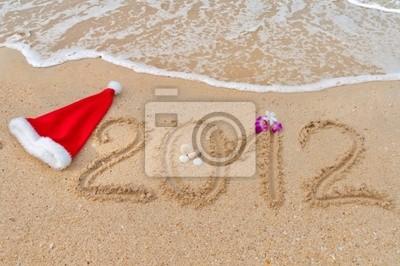 Números 2012 y sombrero de santa en arena de playa tropical